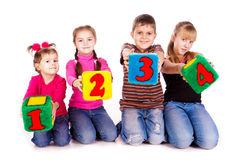 Happy kids holding blocks with numbers. Over white background Royalty Free Stock Images