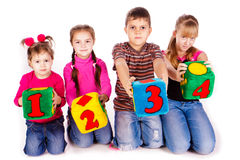 Happy kids holding blocks with numbers. Over white background Stock Image