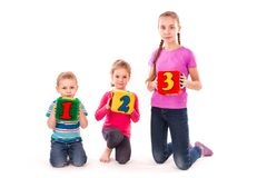 Happy kids holding blocks with numbers over white background. Teamwork concept Stock Images