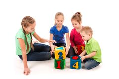 Happy kids holding blocks with numbers over white background. Teamwork concept Stock Image