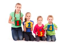 Happy kids holding blocks with numbers over white background. Teamwork concept Stock Photo