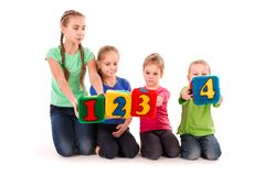 Happy kids holding blocks with numbers over white background. Teamwork concept Royalty Free Stock Photo