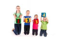 Happy kids holding blocks with numbers over white background Stock Photos