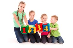 Happy kids holding blocks with numbers over white background. Teamwork concept Royalty Free Stock Images
