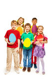Happy kids holding egg shape colourful cards Royalty Free Stock Photos