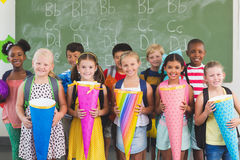 Happy kids holding gifts in classroom stock photos