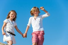 Happy kids holding hands outdoors. Royalty Free Stock Photo
