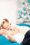 Happy kids hugging near the Christmas tree. Royalty Free Stock Photo