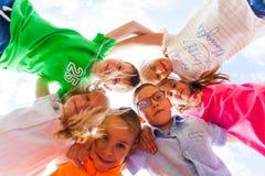 Happy kids hugging on shoulders looking down royalty free stock photo