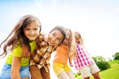 Happy kids hugging toggether. Group of little 6 and 7 years old smiling kids smiling standing outside in the park Royalty Free Stock Images
