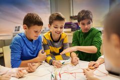 Happy kids with invention kit at robotics school. Education, children, technology, science and people concept - group of happy kids with invention kit at Stock Images