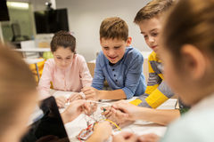 Happy kids with invention kit at robotics school. Education, children, technology, science and people concept - group of happy kids with invention kit at Stock Photo