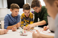 Happy kids with invention kit at robotics school. Education, children, technology, science and people concept - group of happy kids with invention kit at Royalty Free Stock Photo