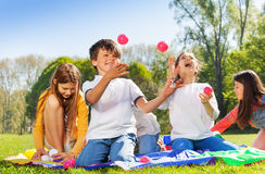 Happy kids juggling with little balls in the park. Portrait of happy kids sitting on the grass in the park and juggling with colorful balls stock photos