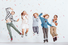 Happy kids jumping. Happy group of kids jumping in a room with decorative tape on the wall stock image