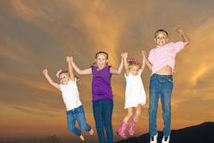 Happy Kids Jumping Together. Four young children having fun together and jumping in the air. Beautiful sunset background Stock Images