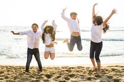 Happy kids jumping together on the beach royalty free stock images
