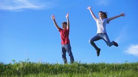 Happy kids jumping together on green grass hill against blue sky stock video