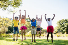 Happy kids jumping together during a sunny day Stock Image