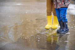 Happy kids jumping under the rain. Closeup of yellow water boots Stock Photo