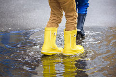 Happy kids jumping under the rain. Closeup of yellow water boots Stock Images