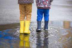 Happy kids jumping under the rain Royalty Free Stock Image