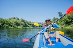 Happy kids kayaking on the river on a sunny day during summer vacation royalty free stock photo