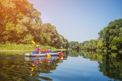 Happy kids kayaking on the river on a sunny day during summer vacation royalty free stock image