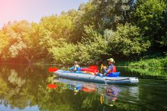 Happy kids kayaking on the river on a sunny day during summer vacation stock photography