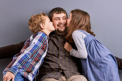 Happy kids kissing their happy father. Portrait of two happy kids kissing their smiling father. Beautiful happy father with his little son and dauughter Stock Image
