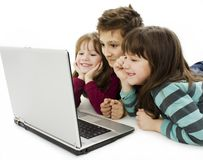 Happy kids with laptop computer. Isolated Stock Image