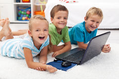 Happy kids with laptop computer. Laying on the floor Stock Photo