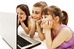 Happy kids with laptop computer. Isolated on white background Stock Photos