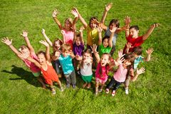 14 happy kids. Large group of happy kids, boys and girls, with lifted hands about 10 years old standing on the green grass top view Royalty Free Stock Images