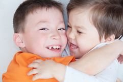 Happy kids, laughing children hugging each other, closeup portrait of boy and little girl, happiness in childhood Royalty Free Stock Photo