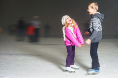 Happy kids laughing at ice rink outdoor, ice skating Stock Photography