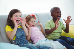 Happy kids laughing while sitting down Stock Photos