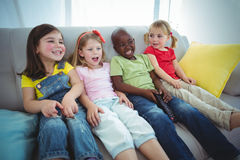 Happy kids laughing while sitting down Royalty Free Stock Photography