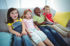Happy kids laughing while sitting down Stock Photo