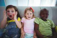 Happy kids laughing while sitting down Stock Image