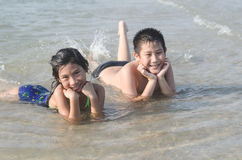 Happy kids laying down in sea, summer concept Stock Photo