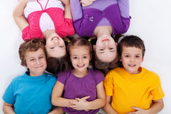 Happy kids laying on the floor. Happy kids - boys and girls - laying on the floor smiling stock photo