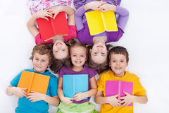Happy kids laying on the floor holding books. The colorful world of reading stock photos
