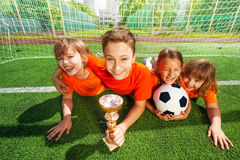 Happy kids laying on grass with golden goblet. And football together Royalty Free Stock Photography