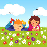Happy kids laying on meadow field grass Royalty Free Stock Photos