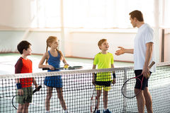 Happy kids learning rules of tennis game. Confident male trainer is explaining how to play tennis to children. Boy is looking at him with aspiration and laughing Royalty Free Stock Image