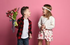 Happy kids: little boy with a bouquet of spring flowers and little girl in pink spring dress and wreath of flowlook at each other. On pink background royalty free stock photography