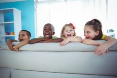 Happy kids looking from the back of the couch Royalty Free Stock Image