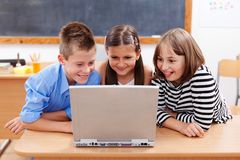 Happy kids looking at laptop stock photography