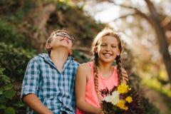 Happy kids in love sitting in a park stock photo